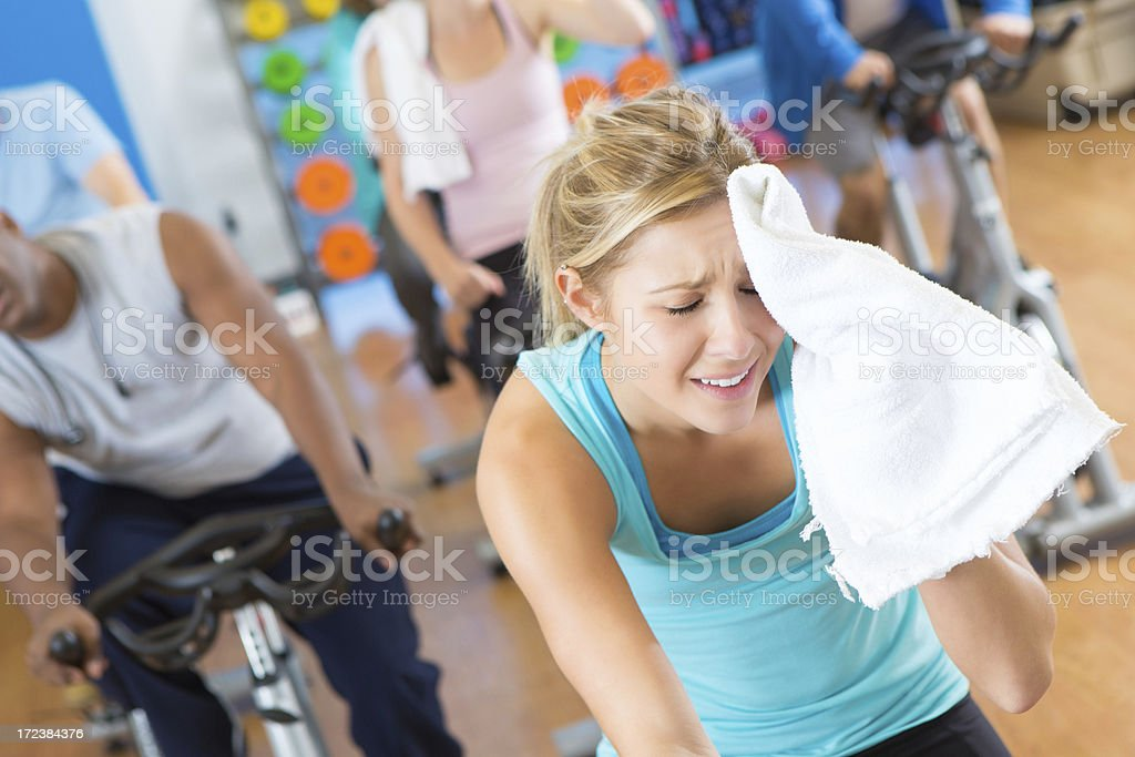 Exhausted woman wiping sweat from forehead during hard cycling workout royalty-free stock photo