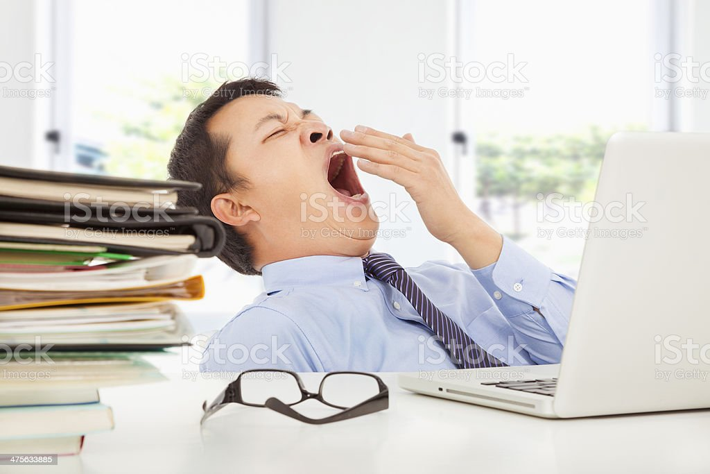 Exhausted young businessman yawning at work stock photo
