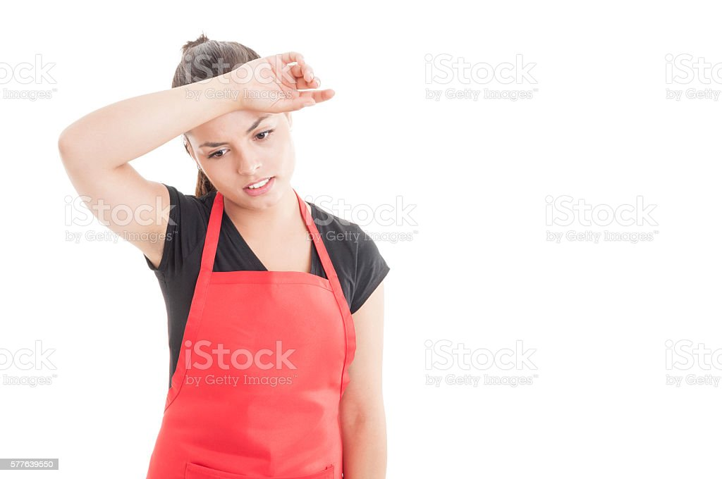 Exhausted young seller with red apron at work stock photo