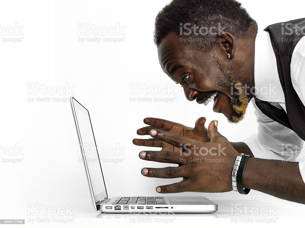 Exhilarated african businessman portrait working at laptop stock photo