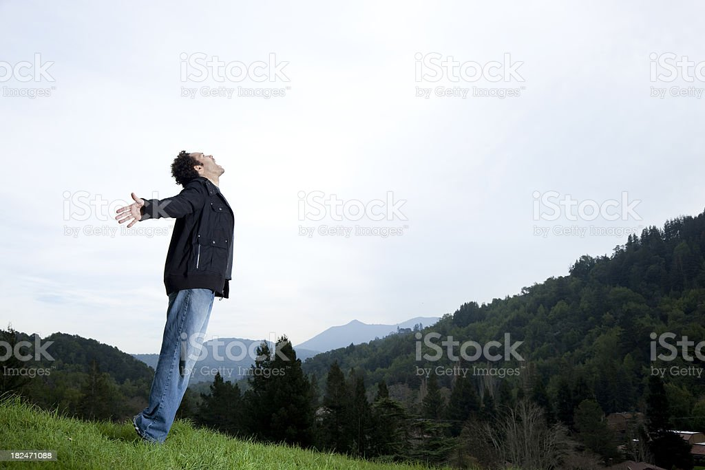 exhilarated man with arms outstretched in nature stock photo