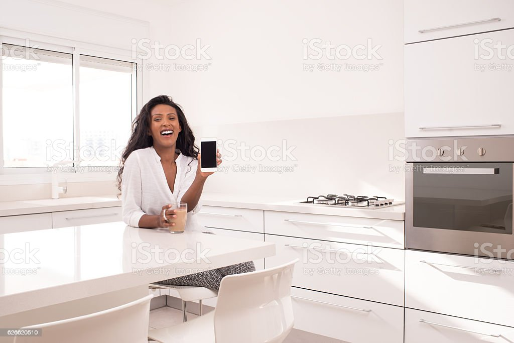 Exited woman showing cellphone, sitting at kitchen. stock photo