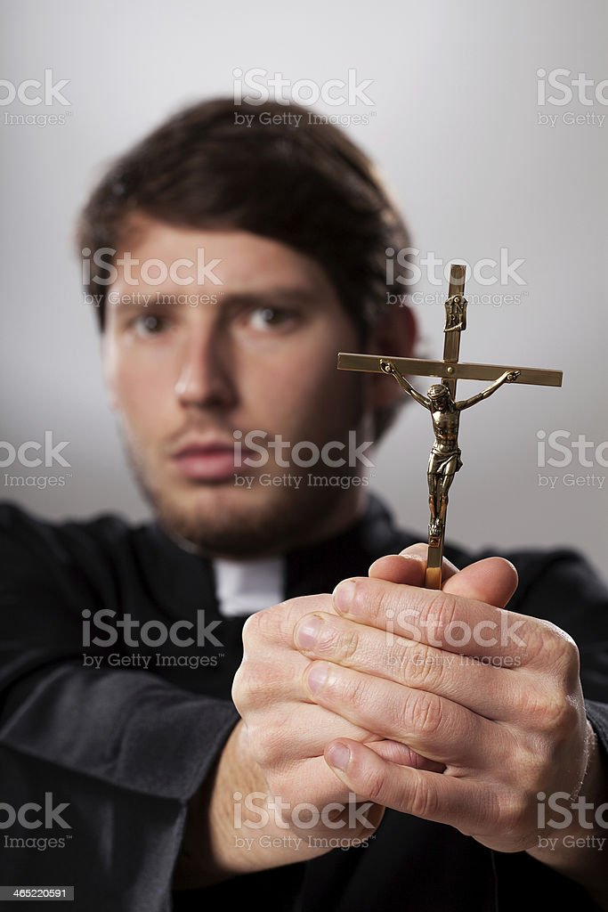 Exorcist with crucifix stock photo
