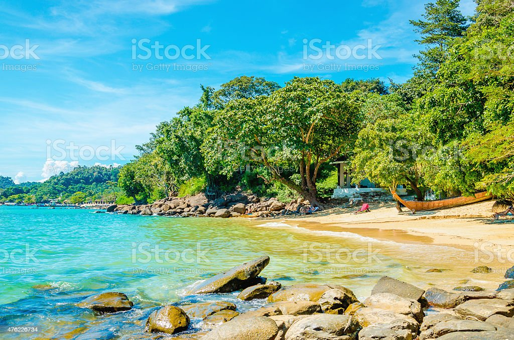 Exotic beach with white sand and high palm trees stock photo