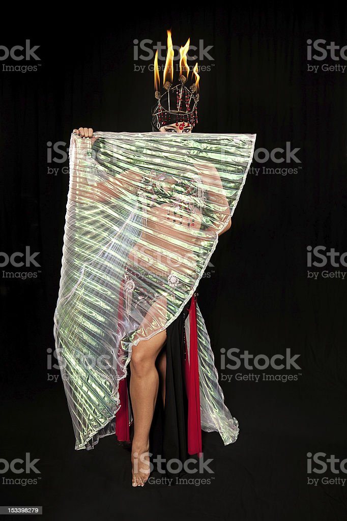Exotic belly dancer with fire headdress and Isis wings stock photo