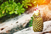 Exotic cocktail in a pineapple on a beach