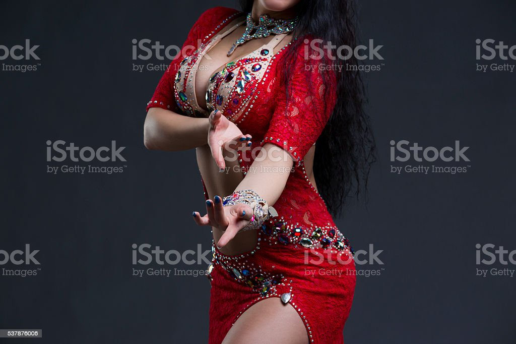 Exotic eastern women performs belly dance in ethnic red dress stock photo