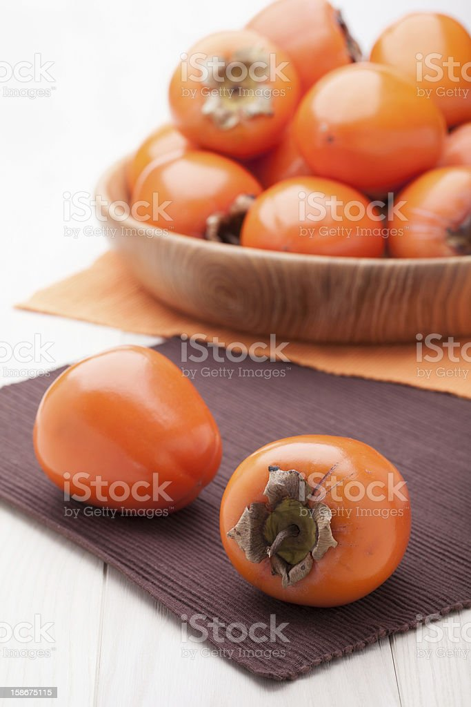 Exotic tropic orange fruits  persimmon served in wooden plate stock photo