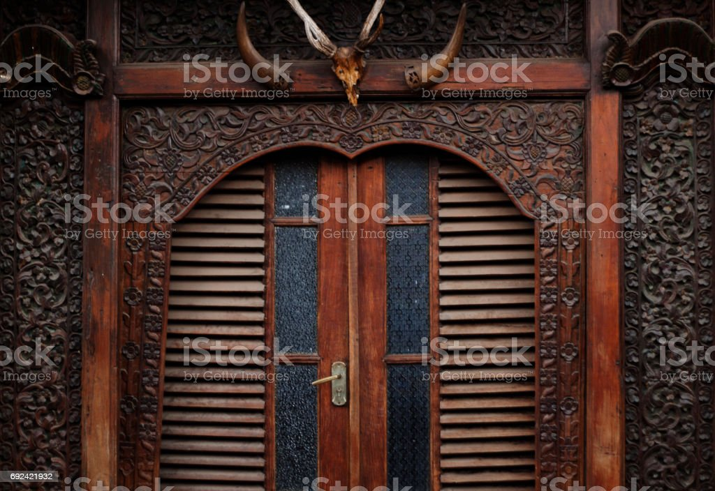 Exotic wood carving in front door of the house stock photo