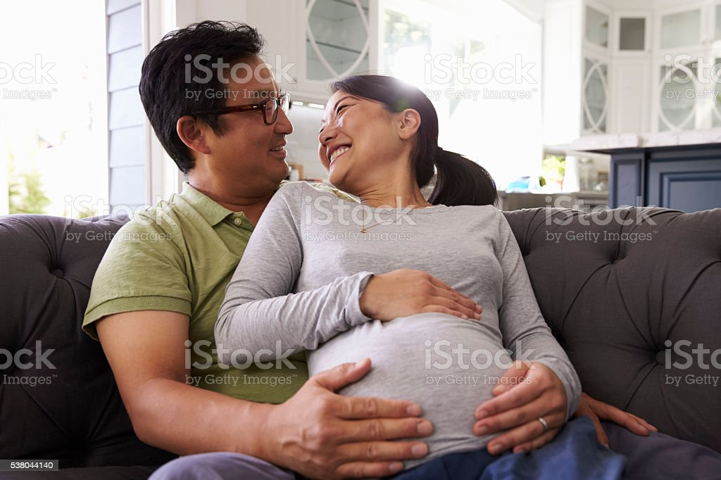 Expectant Couple Relaxing On Sofa At Home Together stock photo