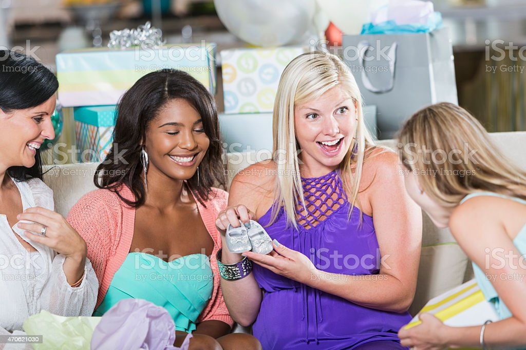 Expectant mom opening presents at baby shower stock photo