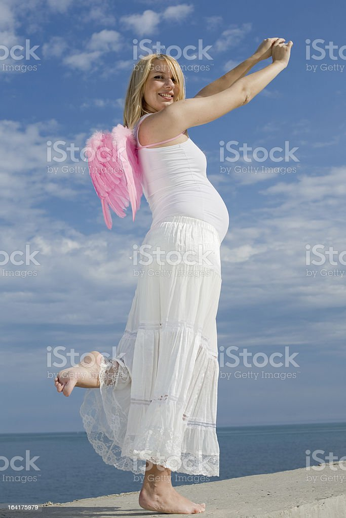 Expectant mother in white on background of sky royalty-free stock photo
