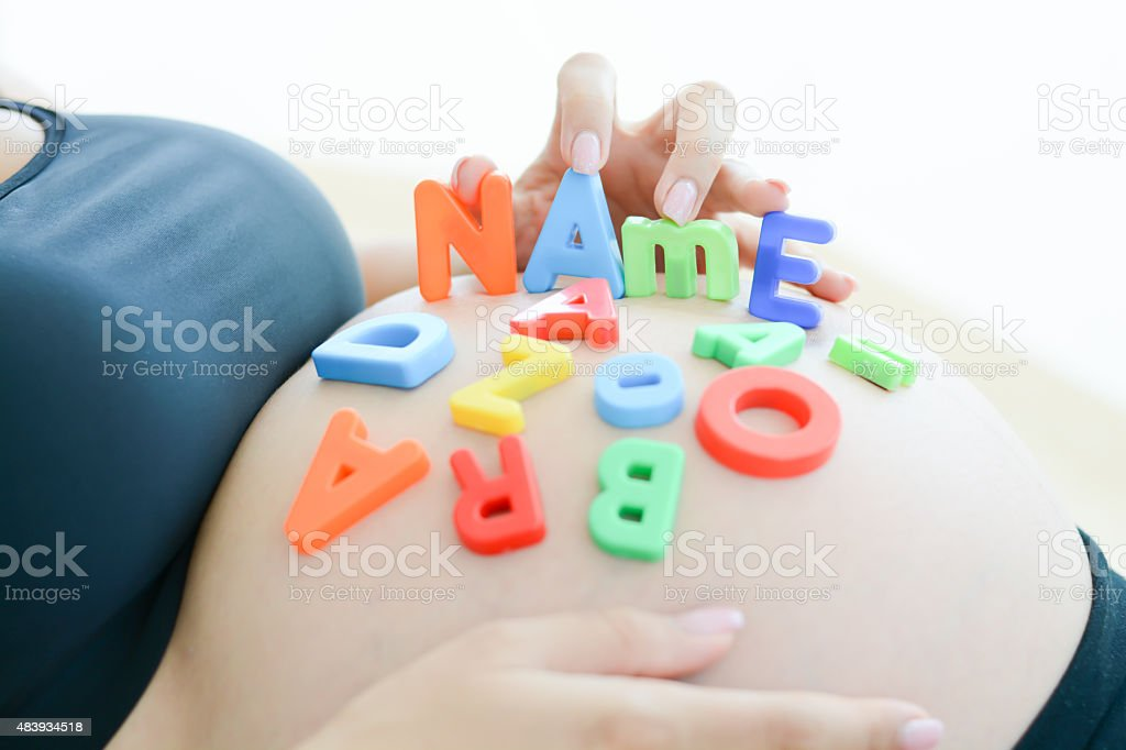 expectant mother spelling name on her pregnant belly stock photo