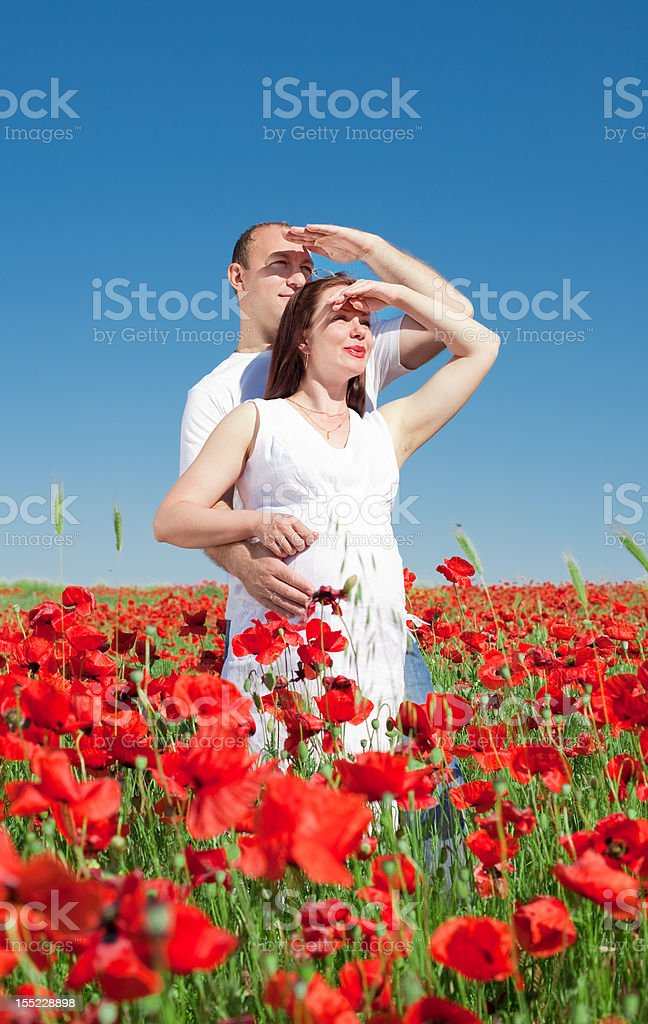 Expectant mother with her husband in poppy field royalty-free stock photo