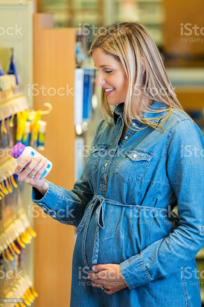 Expecting mother reading label of prenatal vitamins in local pharmacy stock photo
