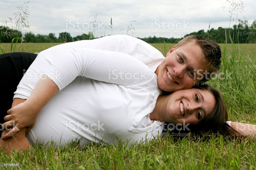 Expecting young couple lying outdoors royalty-free stock photo