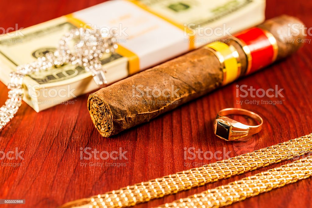 Expensive Cuban cigar and a pack of dollars stock photo
