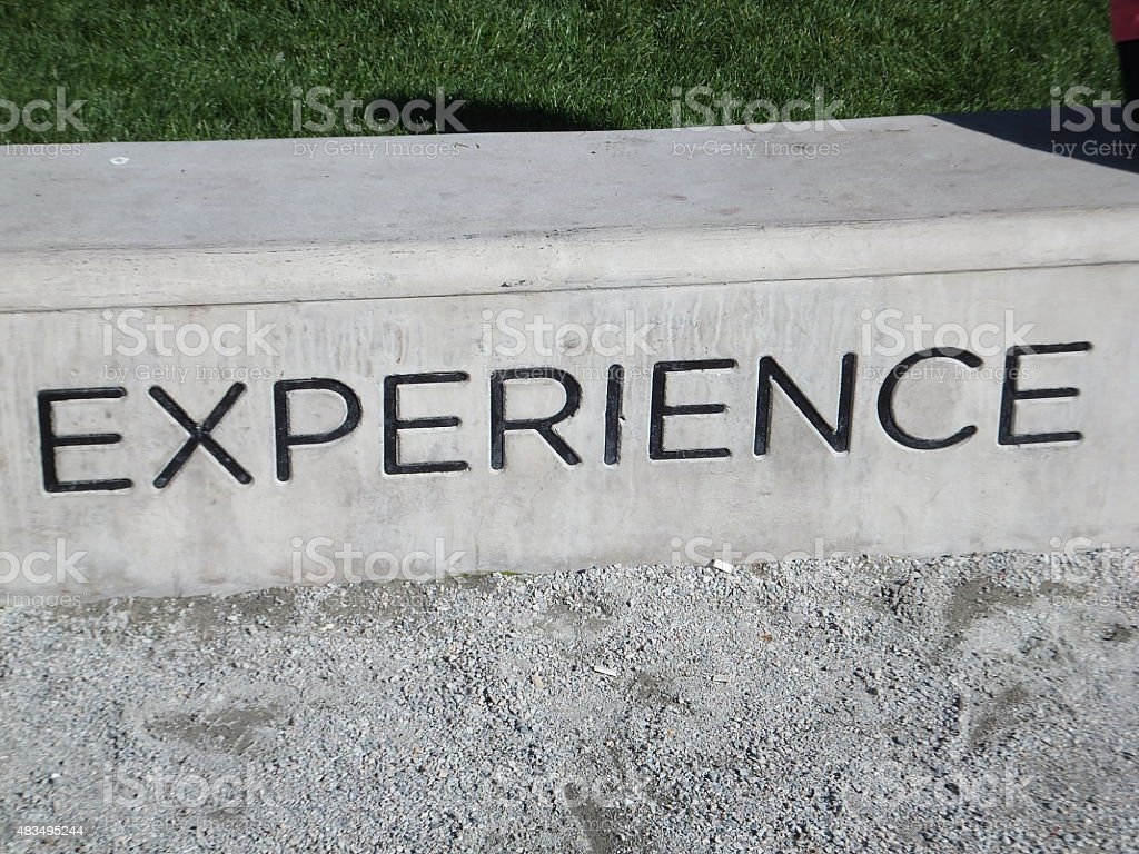 Experience engraved on concrete block stock photo