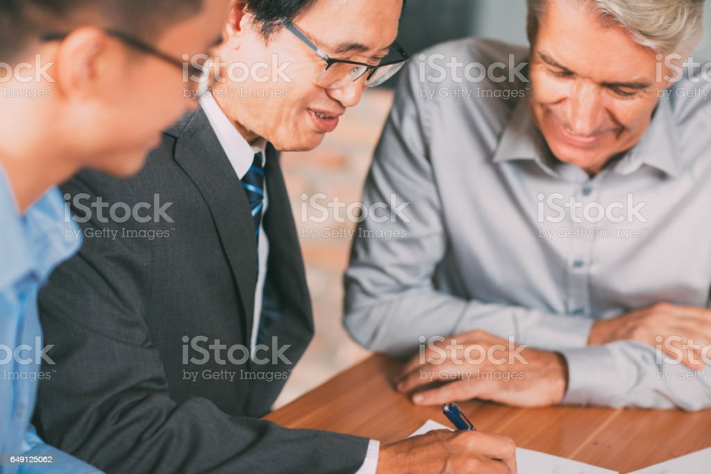 Experienced Asian man arranging merger deal_tone stock photo