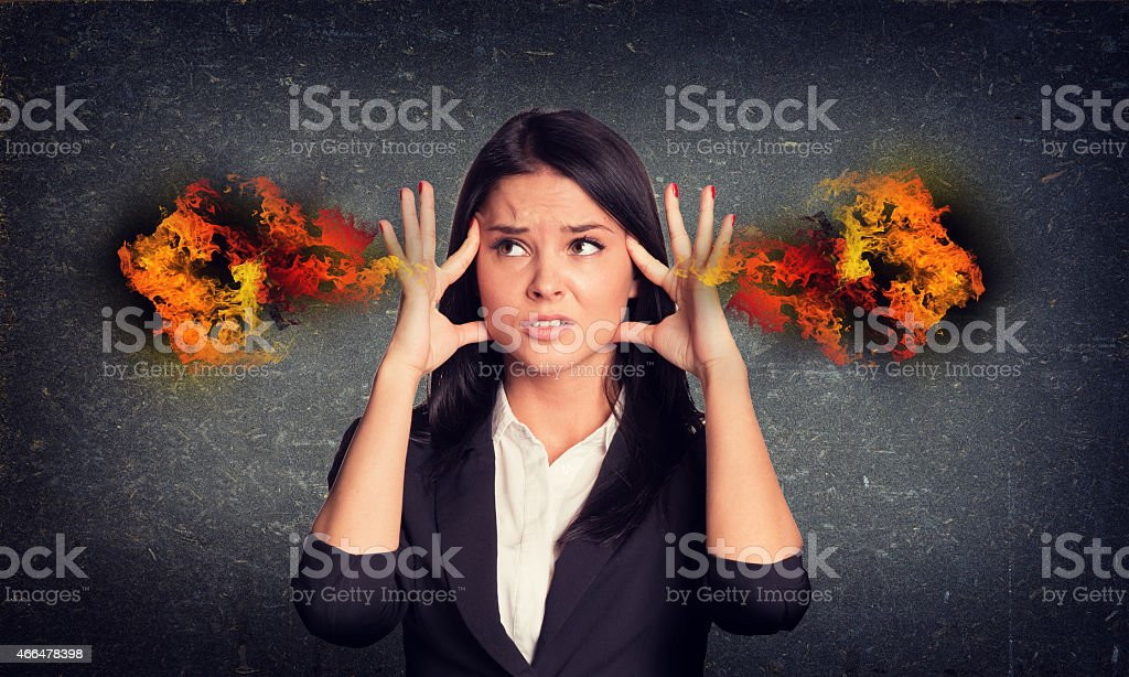 Experiencing woman with fire from ears. Concrete gray wall as stock photo