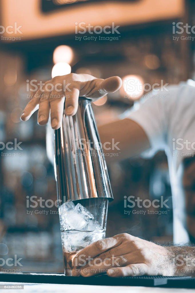 Expert barman making cocktail at night club cocktail shaker. stock photo