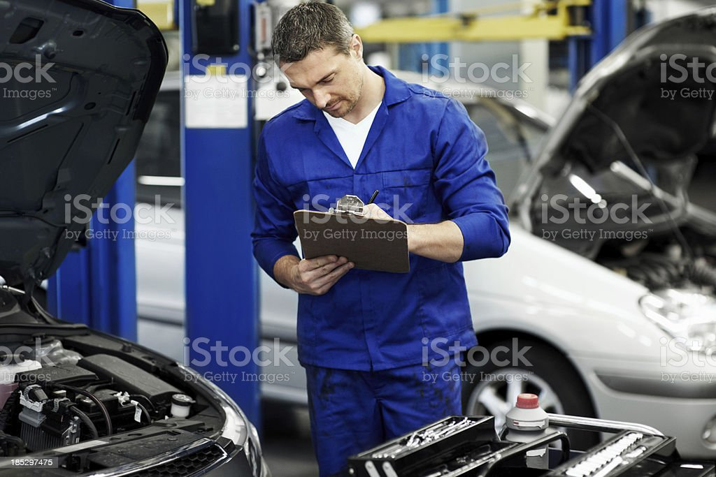 Expert mechanic taking notes royalty-free stock photo
