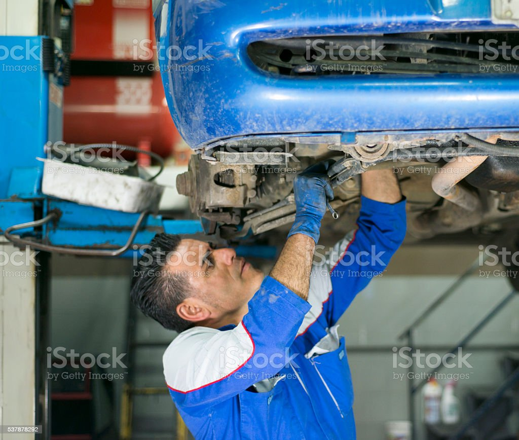 Expert mechanic working in auto repair shop. stock photo