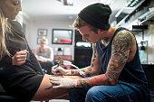 Expert tattooing female customer's lap