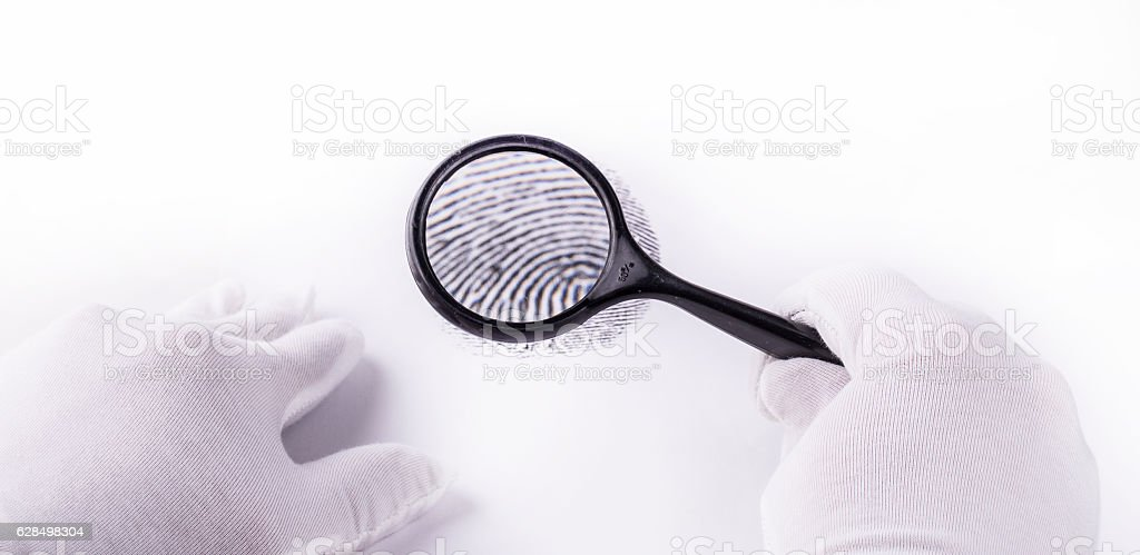 expert through a magnifying glass looking at a fingerprint stock photo