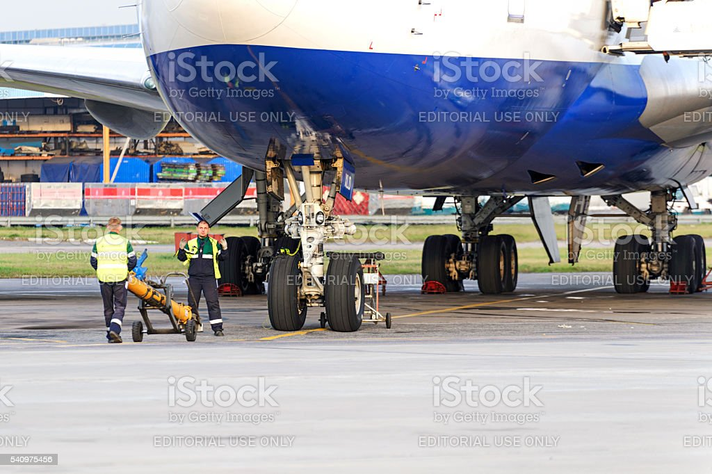 Experts airfield services Domodedovo airport preparing to tow the aircraft stock photo