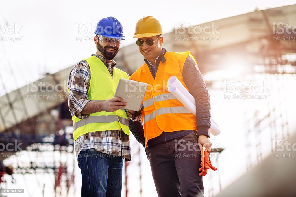Experts having meeting on construction site and using digital tablet stock photo