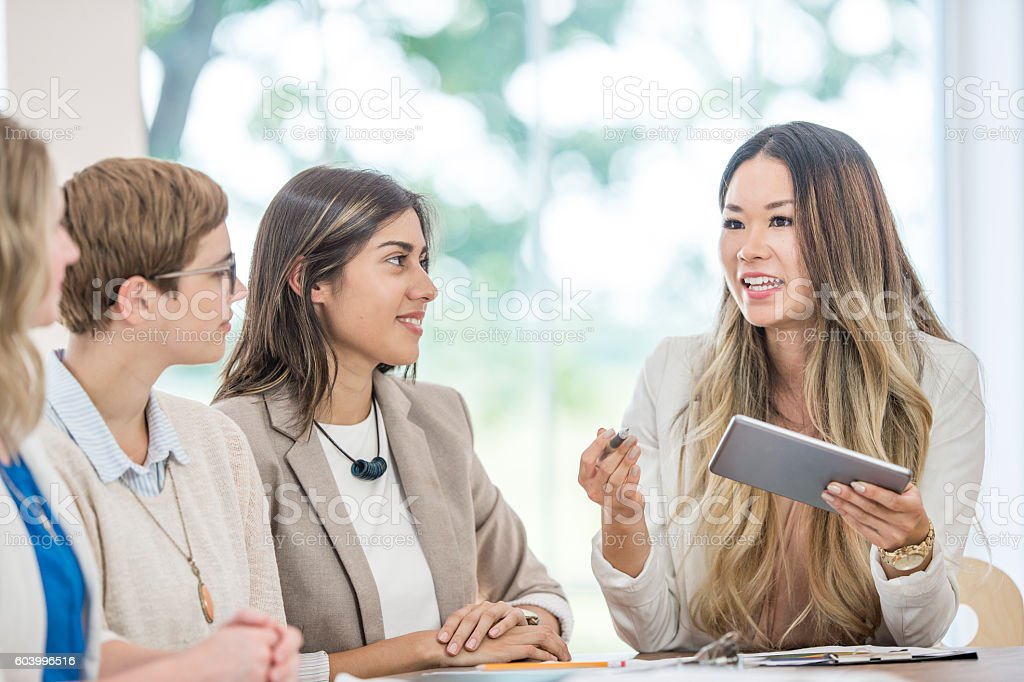 A multi-ethnic group of businesswomen are working together in the...