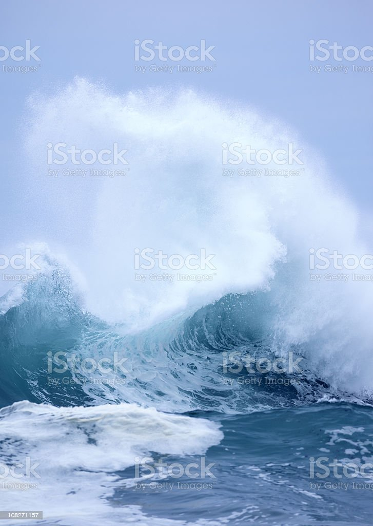 Exploding Wave with white spray and blue clear sky background royalty-free stock photo