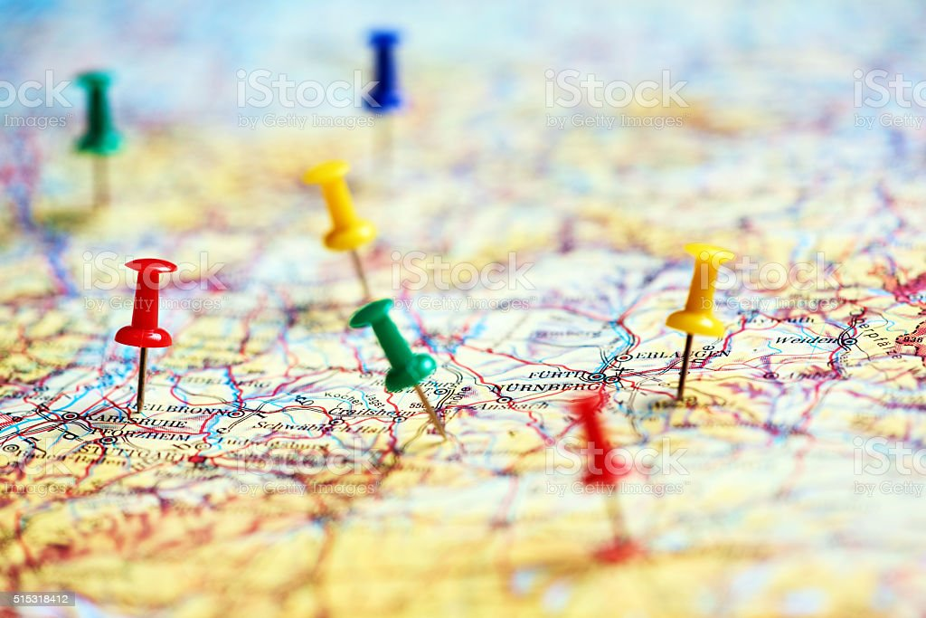 horizontal shot of colorful pins marking different destinations in...