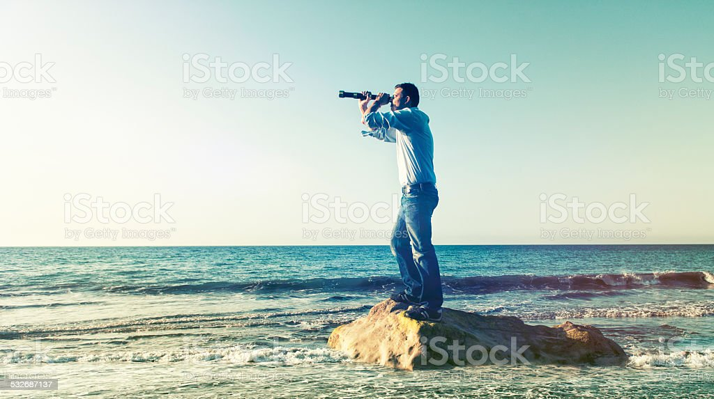 Explorer looking for his next discovery with a hand-held telescope stock photo