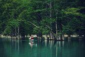 Explorer man kayaking on lake