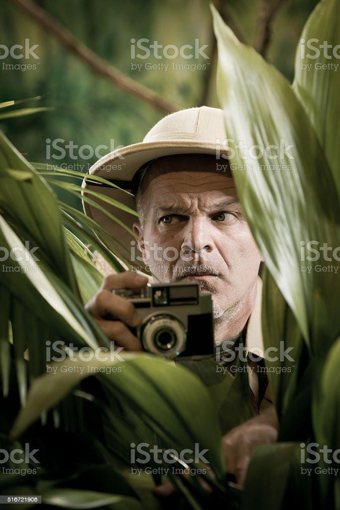 Explorer photographer hiding in vegetation stock photo