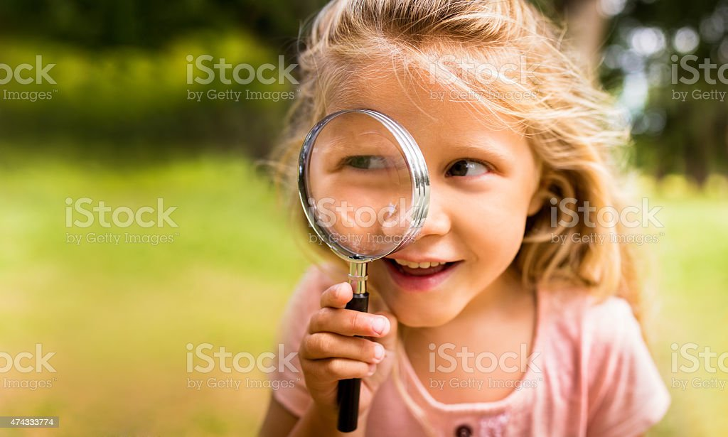 Exploring girl with magnifying glass in nature stock photo