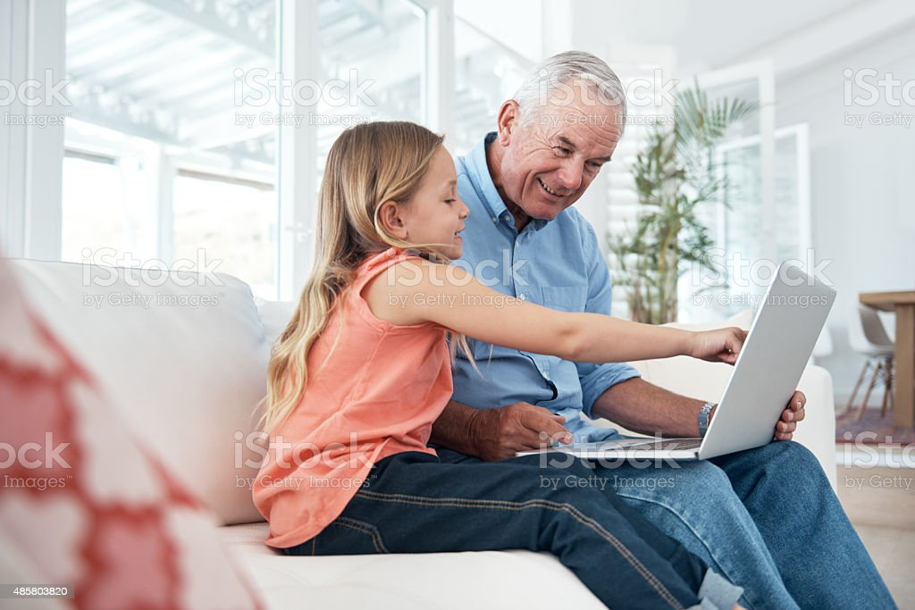 Exploring the online world with grandpa stock photo