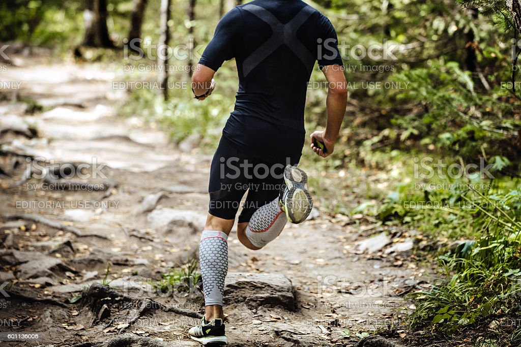 explosive running marathon runner in forest stock photo