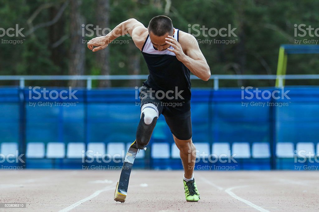 Explosive start of athlete with amputee stock photo