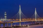 Express roads crosses river icebound, guyed bridge at night lighting.