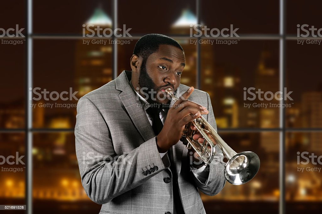 Expressive afro guy playing trumpet. stock photo