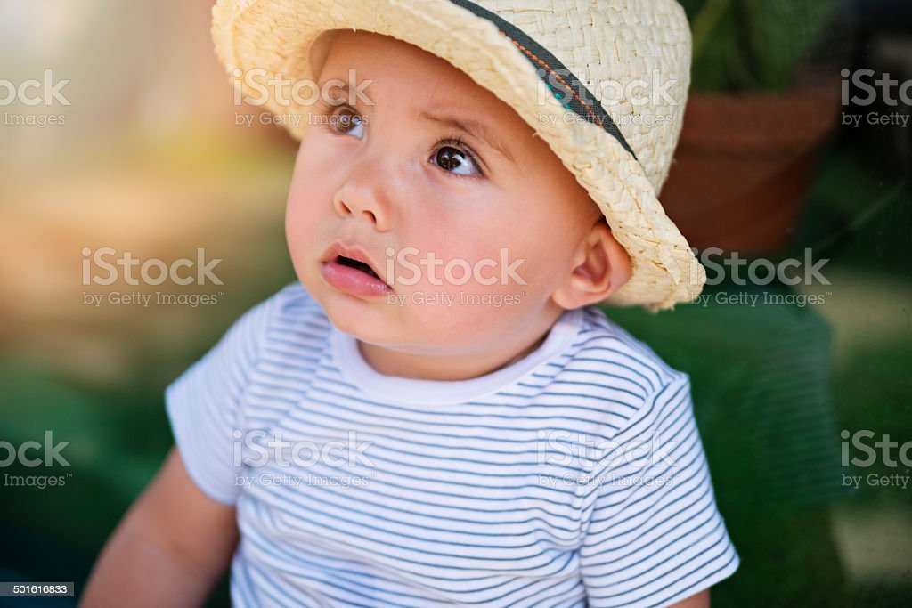 Expressive baby boy swith straw hat looking up. stock photo