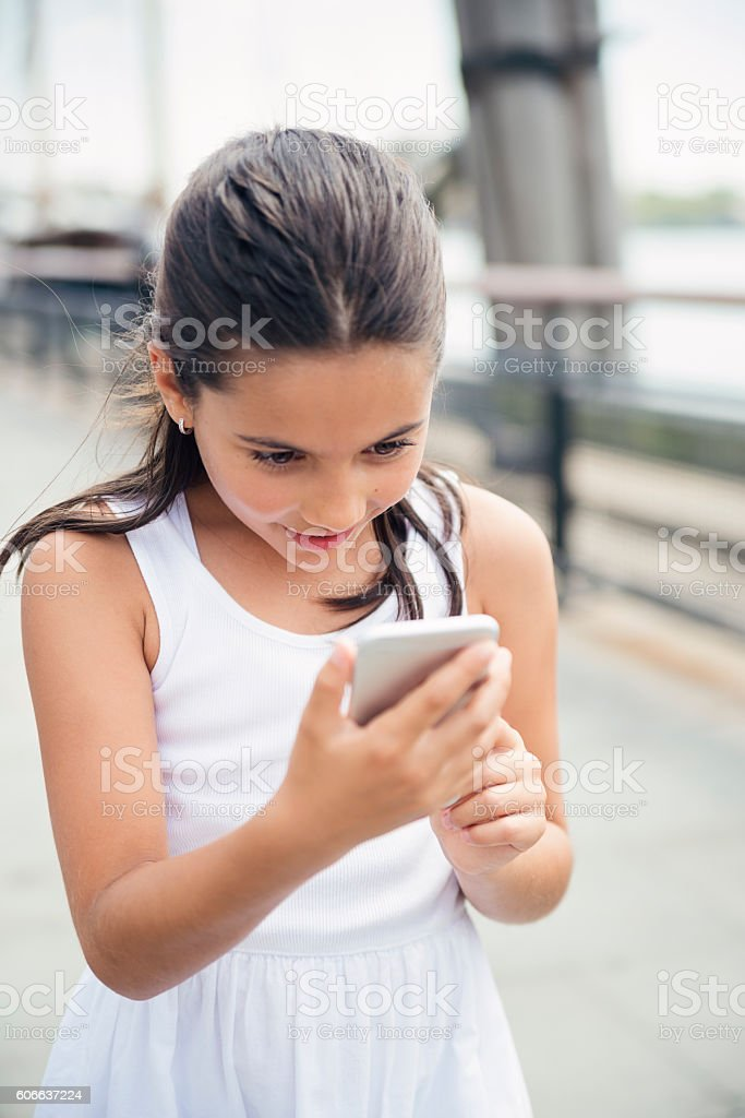 Expressive little girl playing mobile augmented reality game in New-York. stock photo