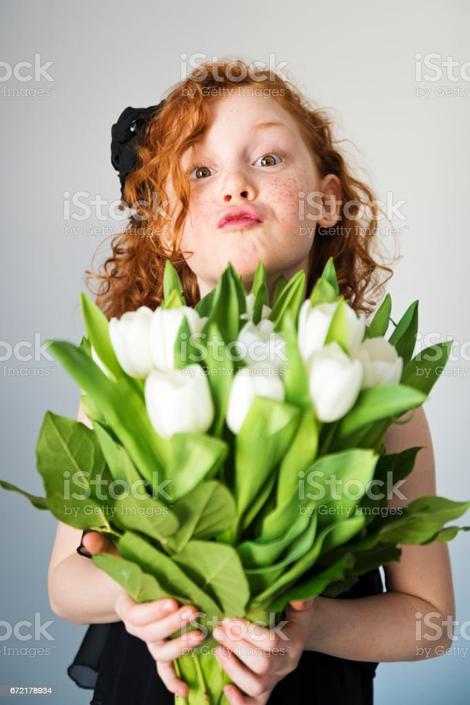 Expressive redhair little girl holding a white tulips bouquet. stock photo