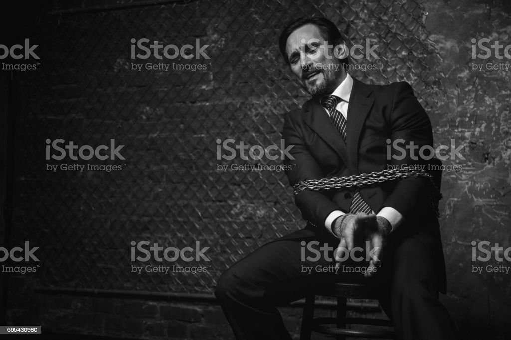 Expressive strong man trying ripping off the chains stock photo