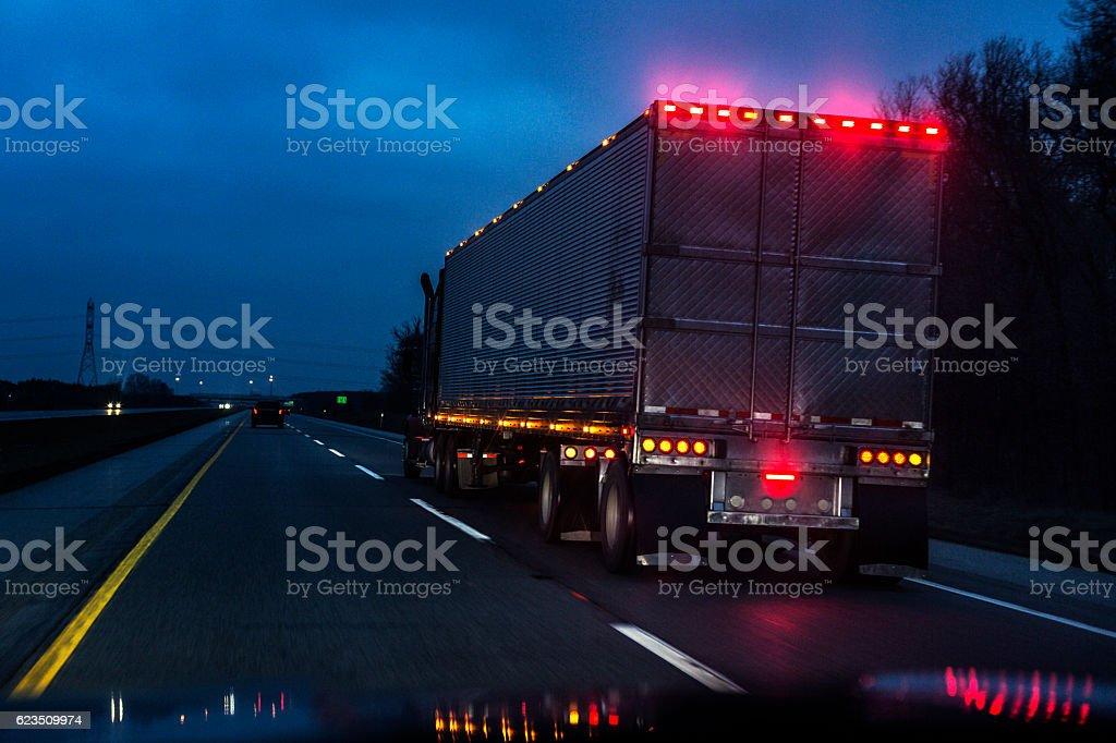 Expressway Speeding Car Driver POV Passing Illuminated Semi Trailer Truck stock photo