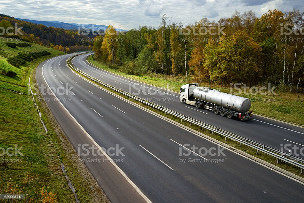 Expressway with driving a silver tanker in the autumn landscape. stock photo