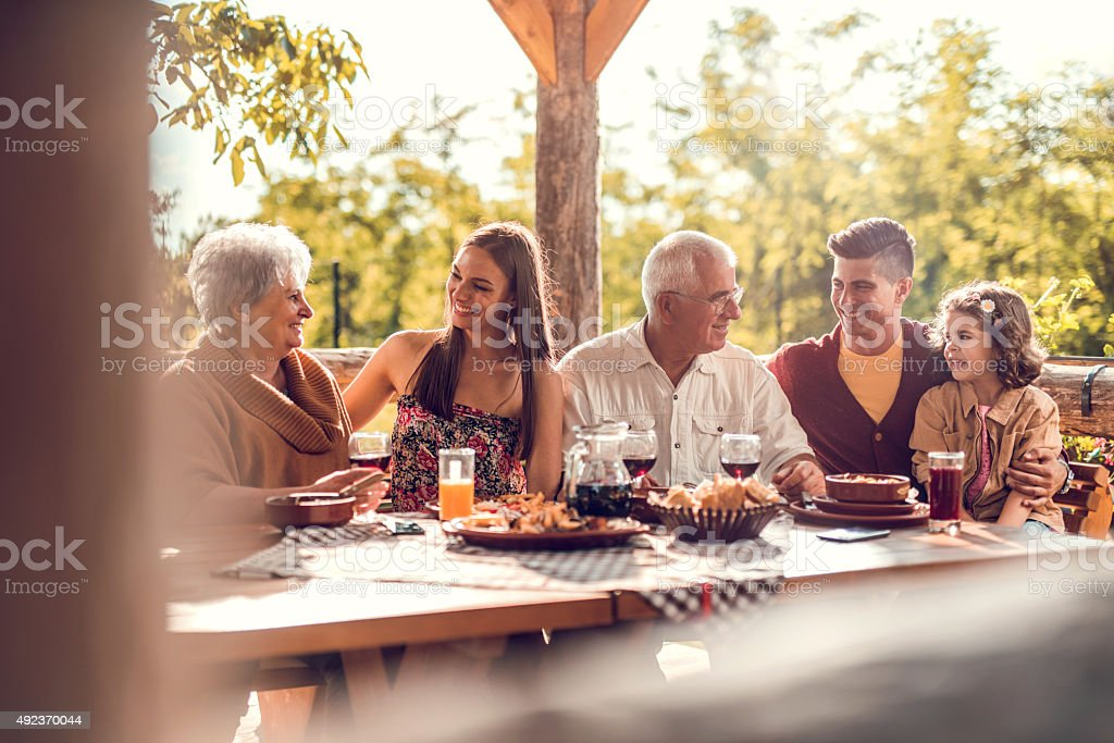 Extended family communicating during a lunch in a restaurant. stock photo